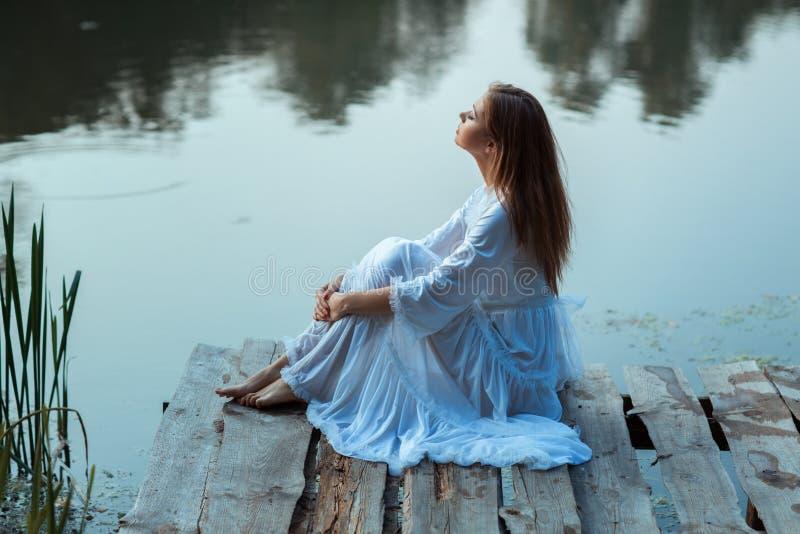 Meisjeszitting op een houten pijler en dromen royalty-vrije stock foto's