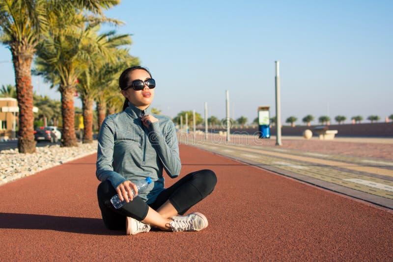Meisjeszitting op een renbaan en het genieten van van zonnige dag royalty-vrije stock fotografie