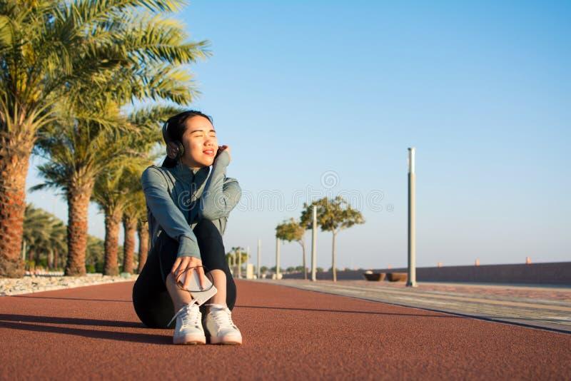 Meisjeszitting op een renbaan en het genieten van van zonnige dag stock afbeeldingen
