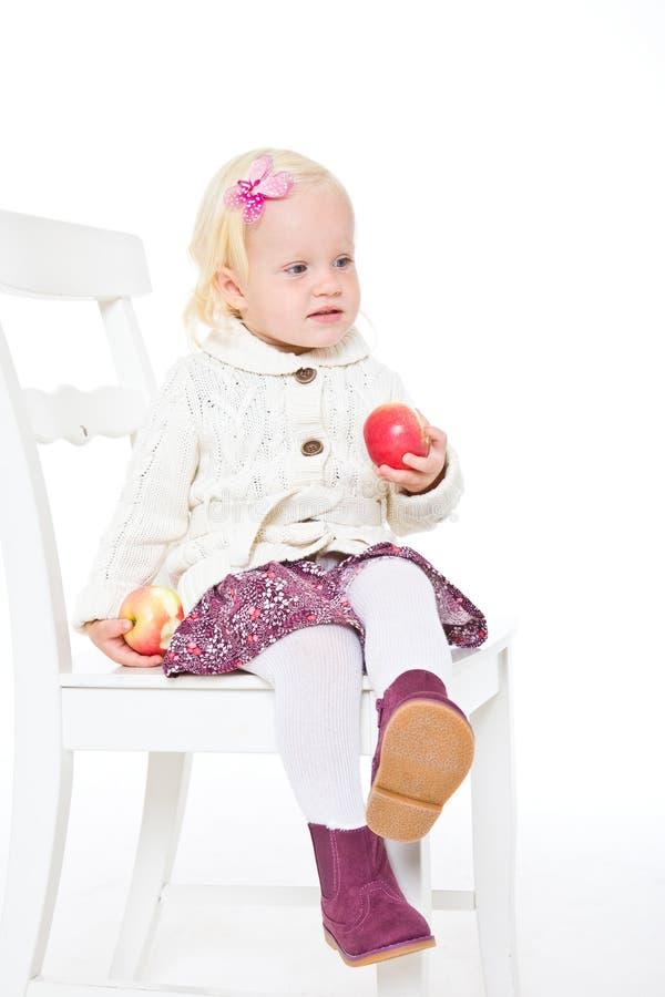 Meisjeszitting op een stoel met rode appelen stock foto's