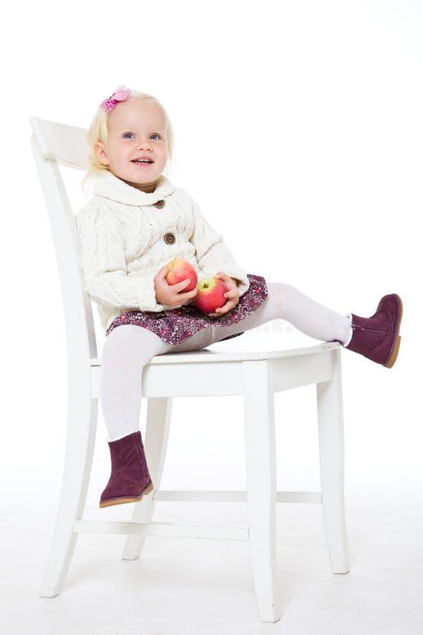 meisjeszitting op een stoel met rode appelen royalty-vrije stock foto