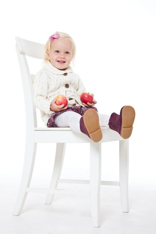 meisjeszitting op een stoel met rode appelen stock fotografie
