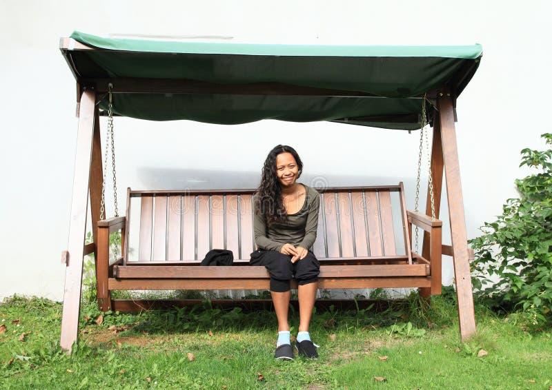Meisjeszitting op een tuinschommeling stock afbeelding