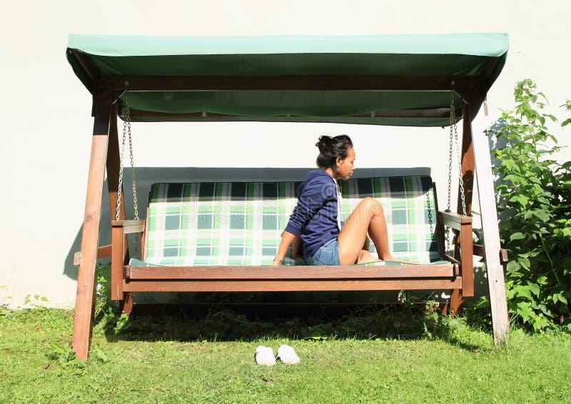 Meisjeszitting op een tuinschommeling stock fotografie