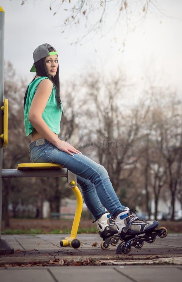 Meisjeszitting op gymnastiekmachine met rolbladen royalty-vrije stock foto's