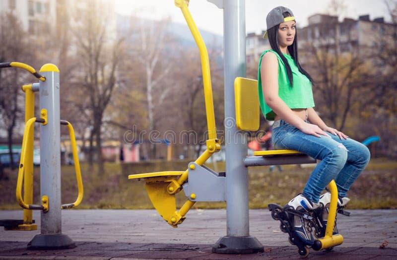 Meisjeszitting op gymnastiekmachine met rolbladen stock afbeelding