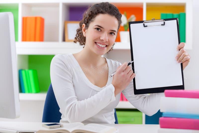 Meisjeszitting op haar bureau die leeg document tonen royalty-vrije stock afbeeldingen