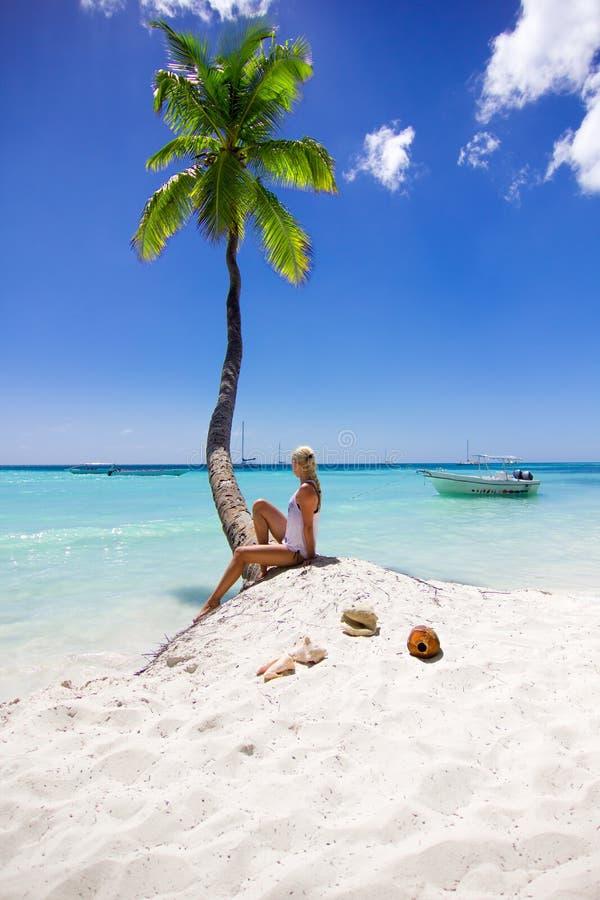 Meisjeszitting op het strand dichtbij palm stock foto