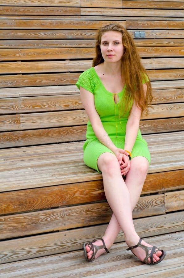 Meisjeszitting op houten treden stock afbeelding