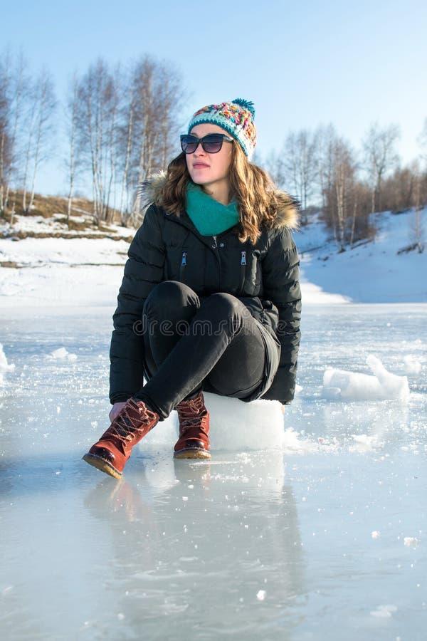 Meisjeszitting op ijsblokje op een bevroren meer stock fotografie