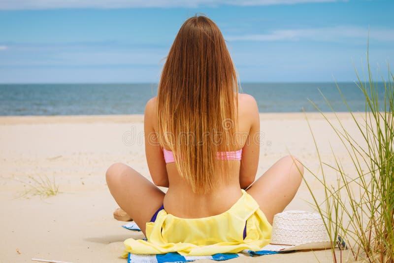 Meisjeszitting op strand die op zee kijken stock foto's