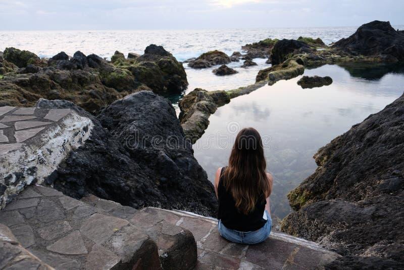 Meisjeszitting op vulkanische rotsen die natuurlijke pool en overzees bekijken stock fotografie