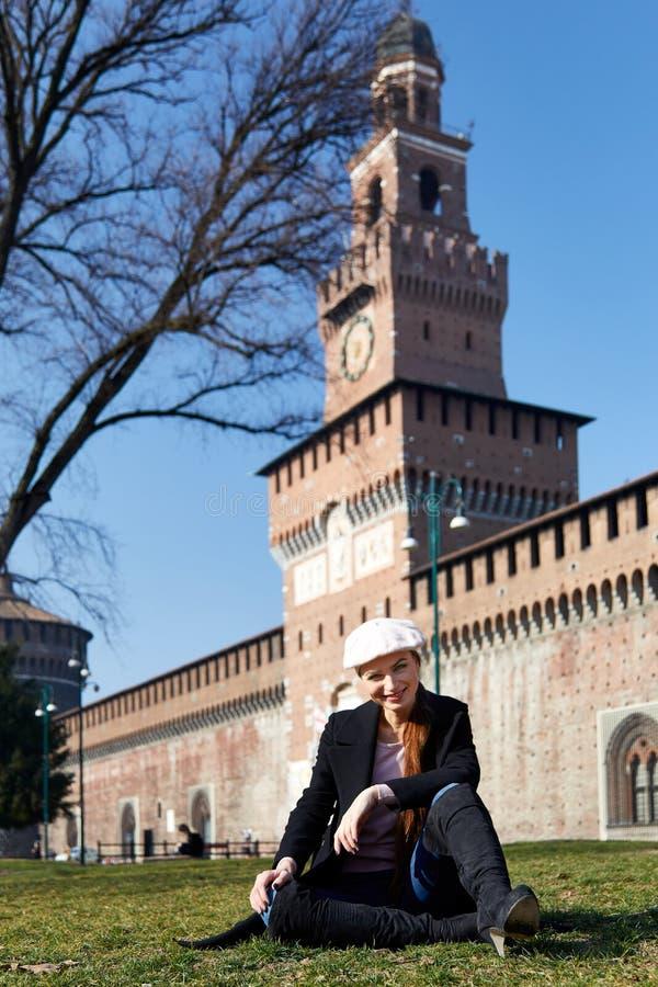 Meisjeszitting voor de glimlach van Castelo Sforzesco voor een portret stock foto's