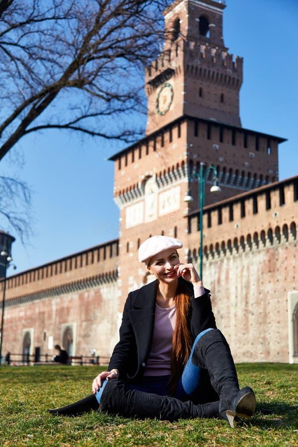 Meisjeszitting voor de glimlach van Castelo Sforzesco voor een portret stock foto