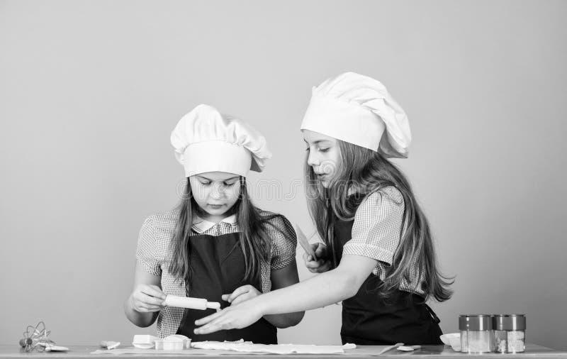 Meisjeszusters die het deeg van de pretgember hebben Jonge geitjes die koekjes samen bakken Jonge geitjesschorten en van chef-kok royalty-vrije stock foto's