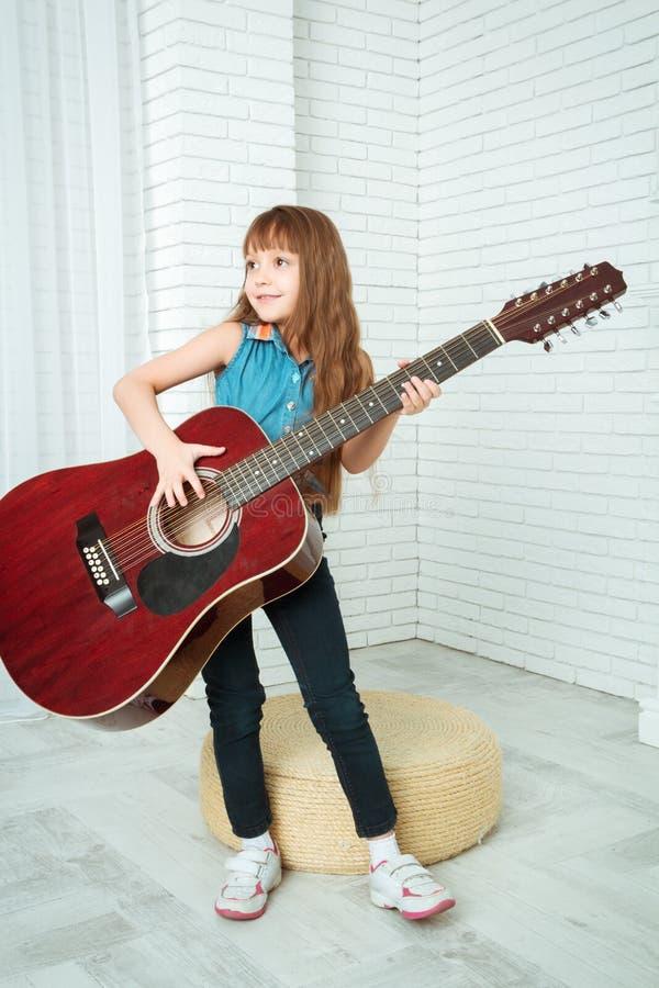 Meisjetribunes met een gitaar stock foto