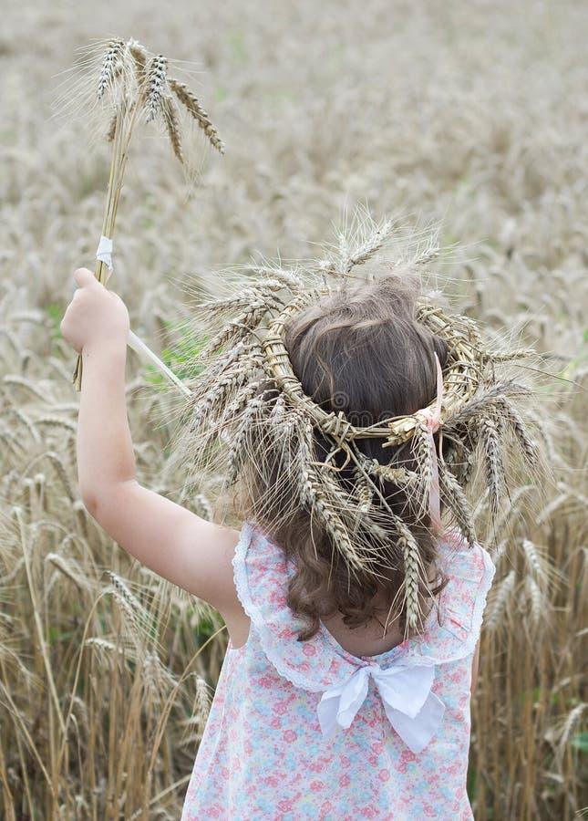 Meisjeverblijf met kroon van tarwe op haar hoofd en holding een boeket van tarwe Achter mening royalty-vrije stock foto