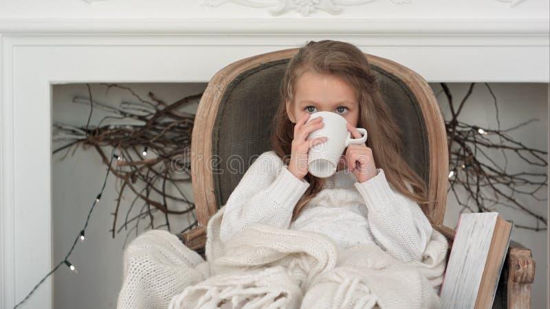 Meisjezitting als comfortabele die voorzitter in een algemene het drinken thee dichtbij Kerstmisopen haard wordt verpakt stock afbeelding