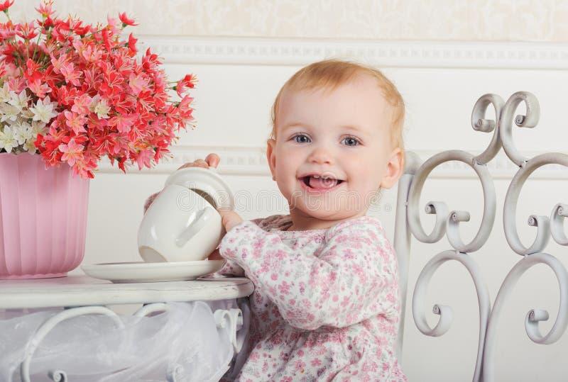 Meisjezitting bij een lijst met thee en decoratie, portrai royalty-vrije stock fotografie