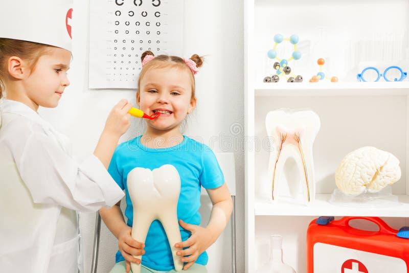 Meisjezitting bij het onderzoek van de tandarts stock afbeelding