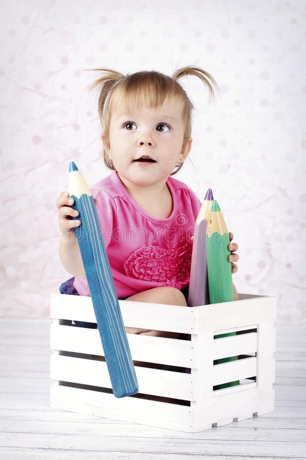 Meisjezitting in de kleine doos met grote kleurende potloden royalty-vrije stock fotografie