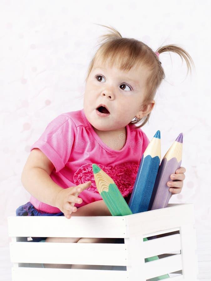 Meisjezitting in de kleine doos met grote kleurende potloden stock foto
