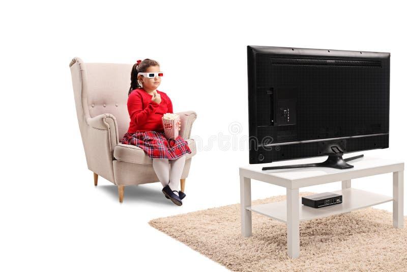 Meisjezitting in een leunstoel met popcorn en het letten van een op film met 3D glazen royalty-vrije stock foto