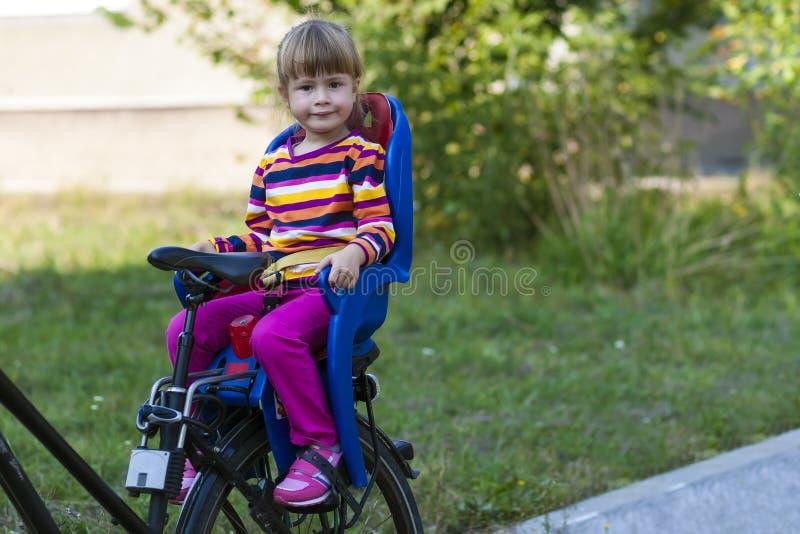 Meisjezitting in fietszetel stock foto's