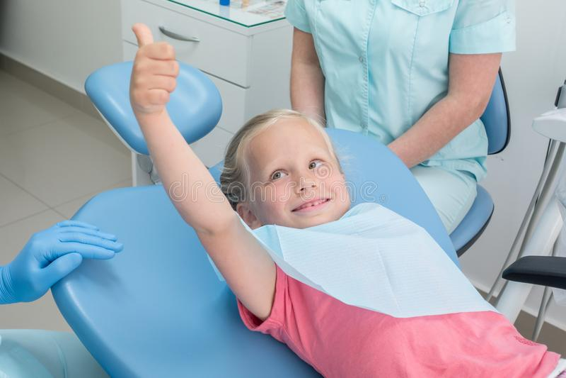 Meisjezitting in het tandartsenbureau stock afbeeldingen