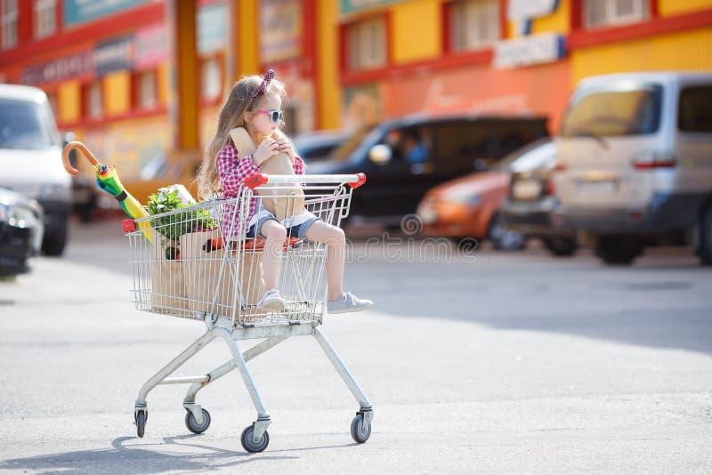 Meisjezitting in het winkelen karretje stock afbeeldingen