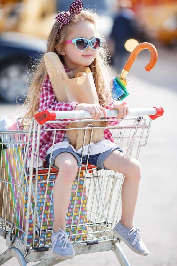 Meisjezitting in het winkelen karretje stock foto's