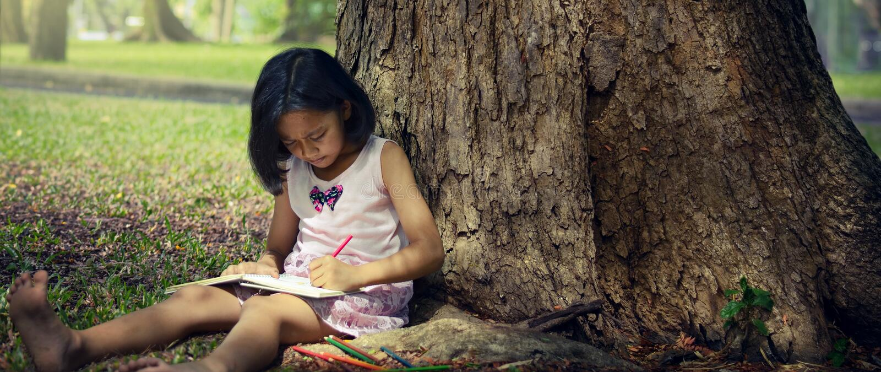 Meisjezitting onder een grote boom en het schrijven van een boek royalty-vrije stock foto