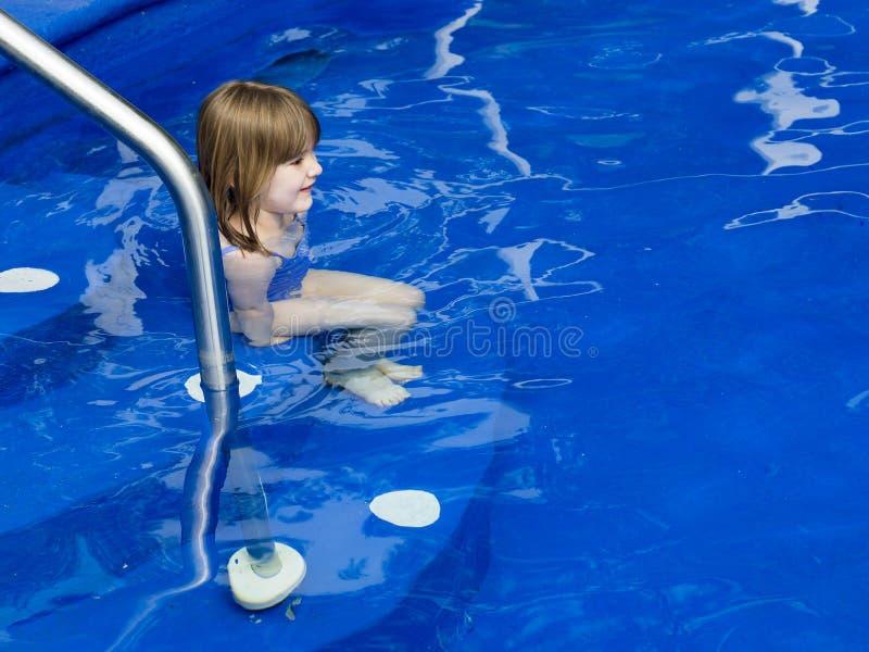 Meisjezitting in ondiep water op de stappen van een diepe blauwe pool royalty-vrije stock foto
