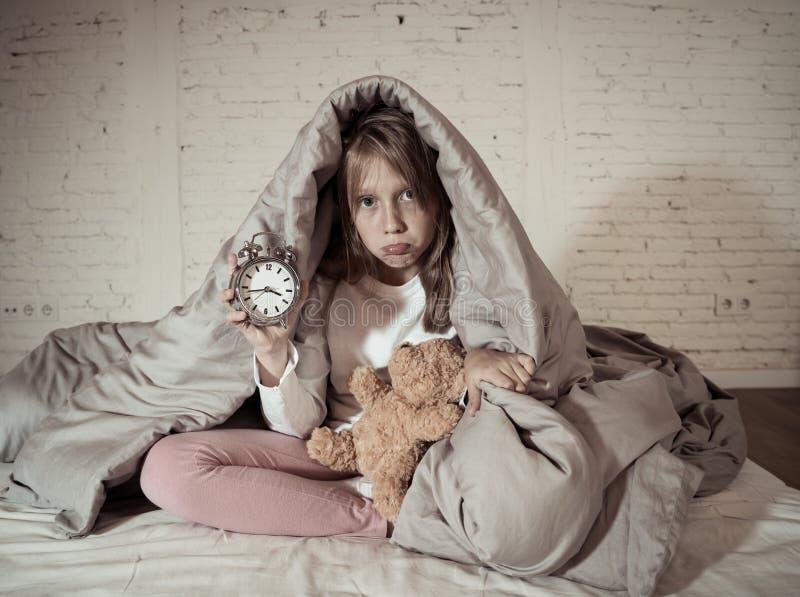 Meisjezitting op bed met teddybeer en wekker slapeloos bij nacht die aan slapeloosheid lijden stock afbeelding