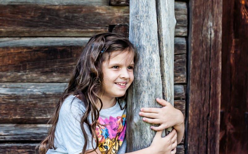Meisjezitting op de portiek van het huis stock afbeelding