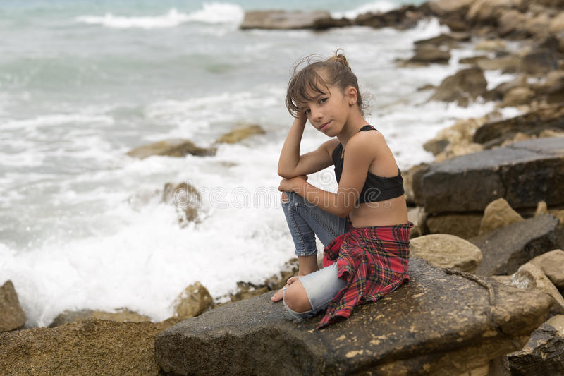Meisjezitting op de rotsen stock afbeelding