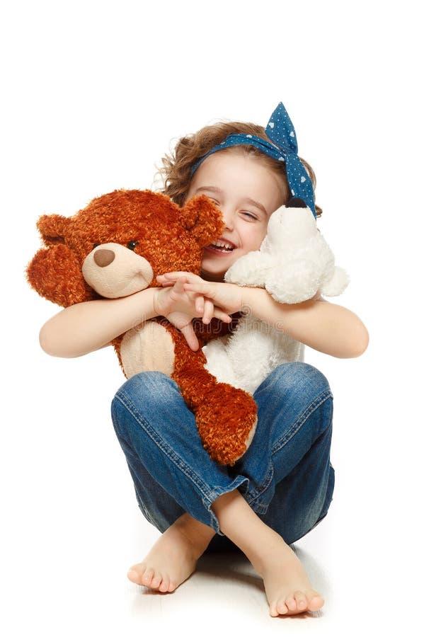 Meisjezitting op de vloer en holding een teddybeer stock afbeelding