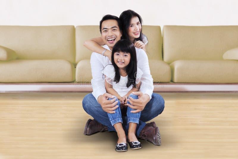 Meisjezitting op de vloer met haar ouders royalty-vrije stock fotografie