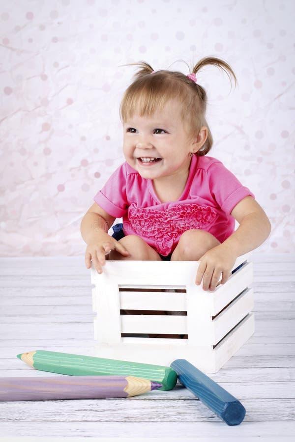 Meisjezitting op het de pluchestuk speelgoed van de bedholding stock afbeeldingen