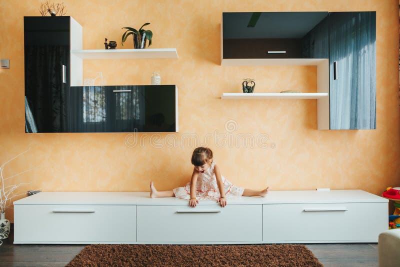 Meisjezitting op streng op meubilair wordt verdeeld dat yoga royalty-vrije stock afbeeldingen