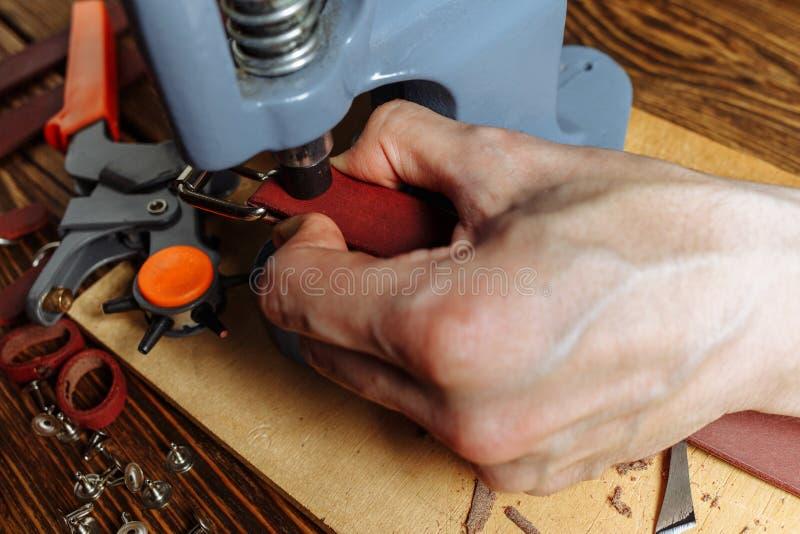 Meister arbeitet an Presse mit Haut Auf braunem Holztisch zerstreute mit Werkzeugen und Zubehör stockbild