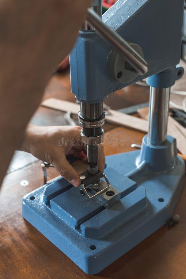 Meister arbeitet an Presse mit Haut Auf braunem Holztisch zerstreute mit Werkzeugen und Zubeh?r lizenzfreies stockbild