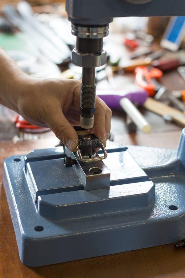 Meister arbeitet an Presse mit Haut Auf braunem Holztisch zerstreute mit Werkzeugen und Zubeh?r lizenzfreie stockbilder