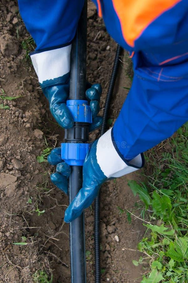 Meister der Wasserversorgung schließt Polypropylenkommunikation im Graben an das Haus, Nahaufnahme an lizenzfreies stockfoto