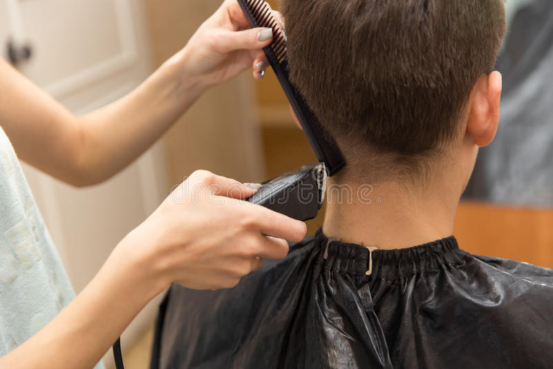 Meister schneidet Haar von Männern im Friseursalon, Friseur macht Frisur für einen jungen Mann stockbild