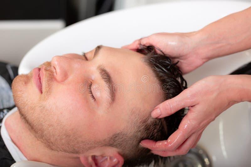 Meister w?scht den Kopf des Kunden im Friseursalon, Friseur macht Frisur f?r einen jungen Mann lizenzfreie stockfotografie