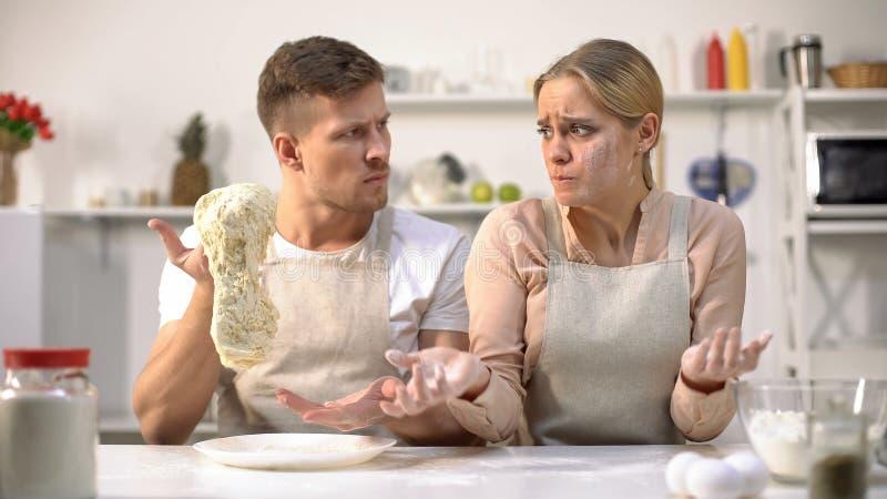 Meisterkoch, der den rohen Teig, unzufrieden gemacht mit Arbeit des neuen Kochs, Beruf ausdehnt lizenzfreie stockfotos