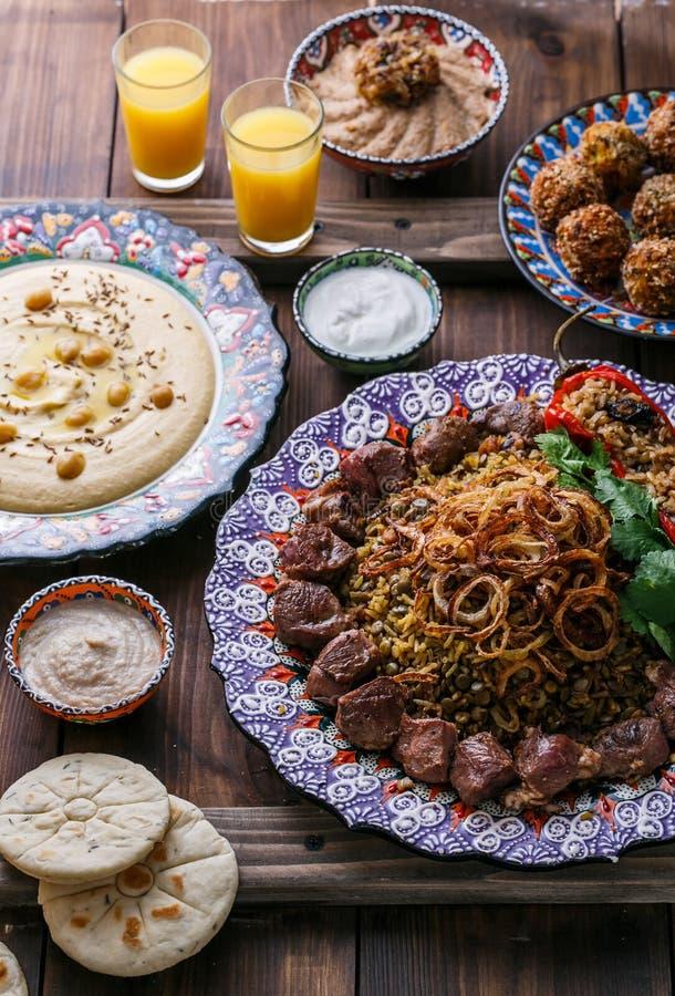 Mejadra с hummus, kashke bademjan и пита, деревянной предпосылкой стоковое фото