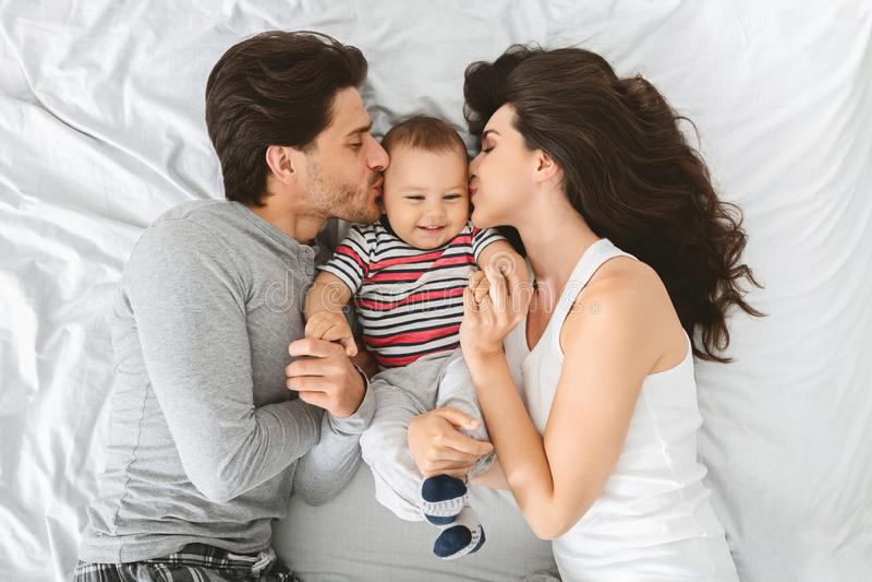 Mejillas dulces que se besan de la pareja caucásica feliz de su hijo adorable del bebé fotografía de archivo libre de regalías