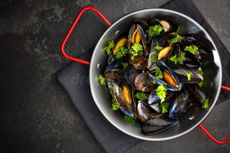 Mejillones con el perejil fresco, plato de los mariscos, visión superior foto de archivo